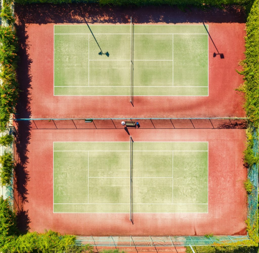 Aerial view of tennis court at sunset in summer. Top view